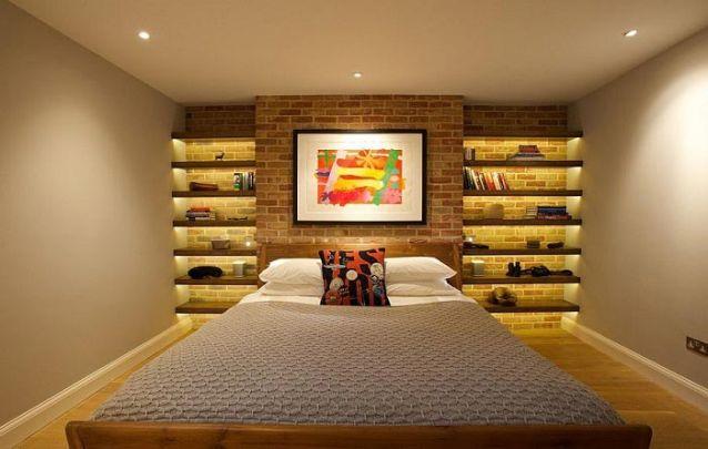 Aqui o espaço vertical atrás da cama foi utilizado de maneira inteligente para aumentar o espaço de apoio no ambiente pequeno