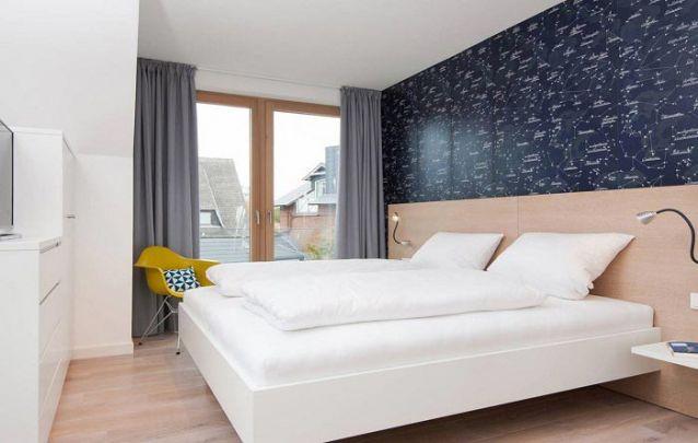 O papel de parede de constelações traz um charme especial para o design do quarto