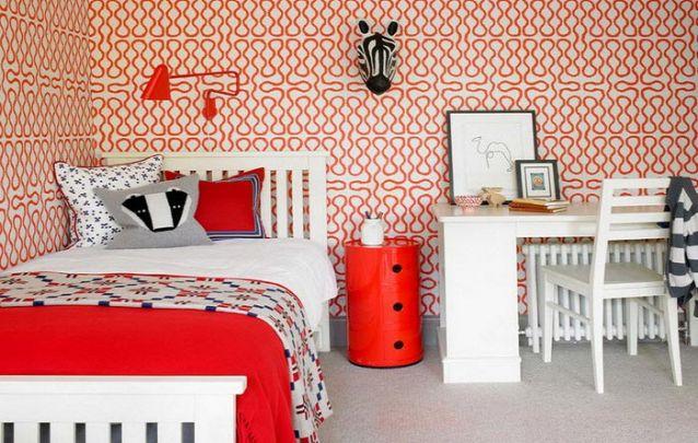 O papel de parede vermelho traz um toque contemporâneo ao quarto de menina