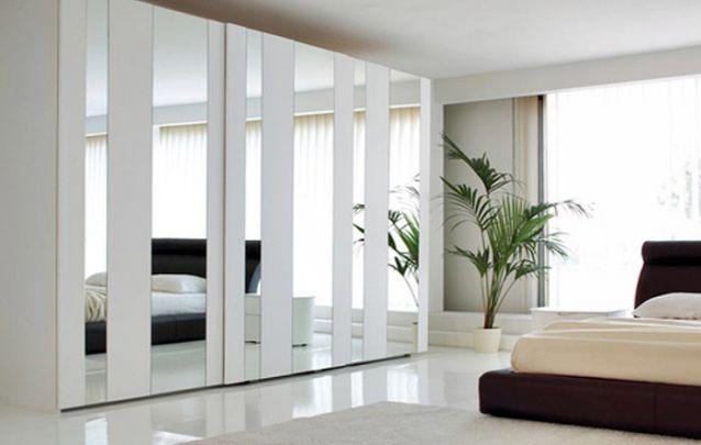 As faixas de espelho deixam o guarda roupa casal planejado contemporâneo e original