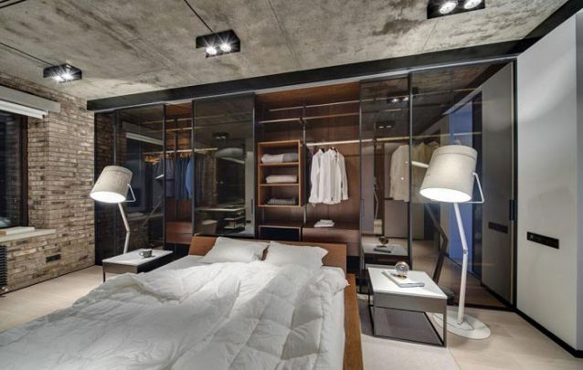 Neste design industrial, o guarda roupa planejado atrás da cama é o destaque do projeto