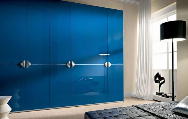 O guarda roupa planejado azul veio para quebrar o padrão de cores neutras do restante do quarto