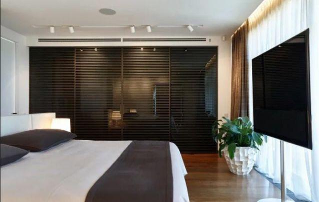 O guarda roupa embutido com portas de vidro preto dão um toque contemporâneo ao quarto do casal