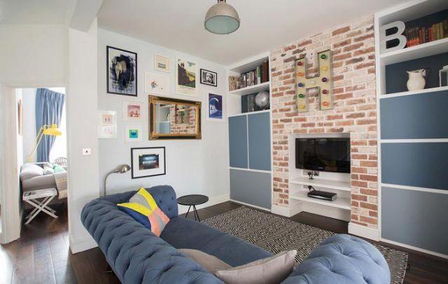 Nesta sala de estar os móveis planejados foram embutidos na parede de tijolos queimados