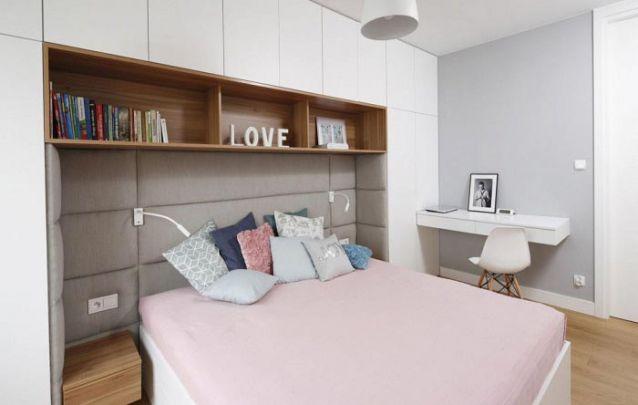 O armário planejado atrás da cama serve como complemento para a cabeceira estofada