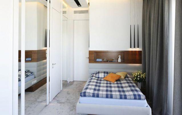 Um quarto com cama de solteiro e móveis planejados para a utilizar da melhor maneira o espaço disponível