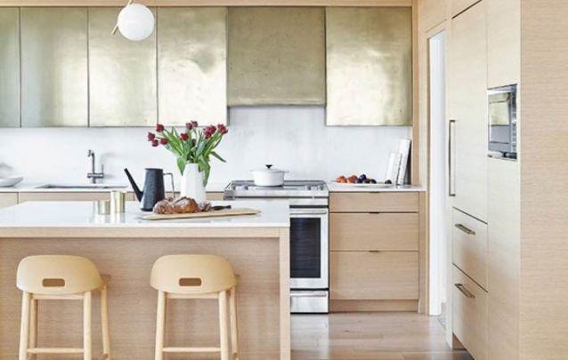 Os armários dourados trazem um toque inusitado para esta cozinha americana com estilo escandinavo