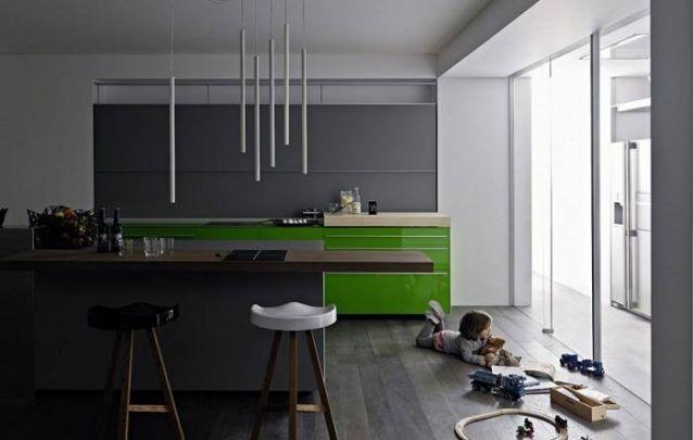 O verde foi a cor escolhida para criar destaque dentro desta cozinha americana predominantemente cinza