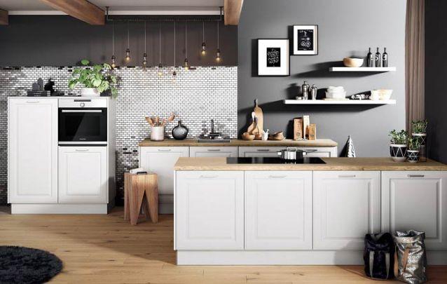 O revestimento metálico na parede valoriza a estética desta cozinha americana