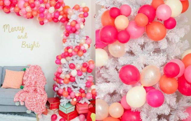 Uma arvore de natal decorada de maneira divertida e em harmonia com os balões da parede