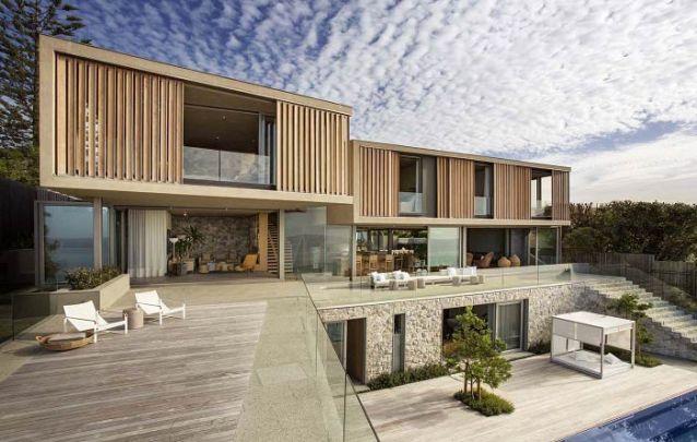 As venezianas em madeira além de trazerem valor estético ao projeto, auxiliam no controle da luminosidade na parte interna da casa