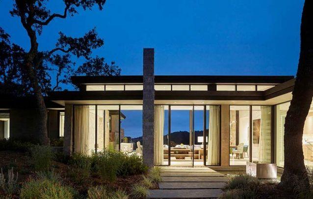 Através do vidro é possível observar os ambientes integrados na parte interna da casa