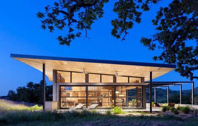 Casa moderna com telhado inclinado e frente toda em vidro