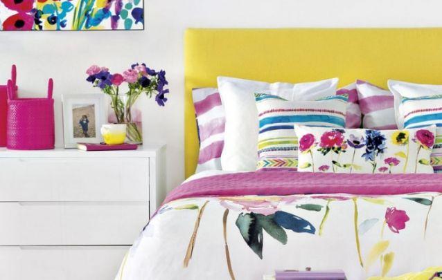 A cabeceira amarela e a roupa de cama estampada, vêm para quebrar a monotonia do branco que prevalece no quarto