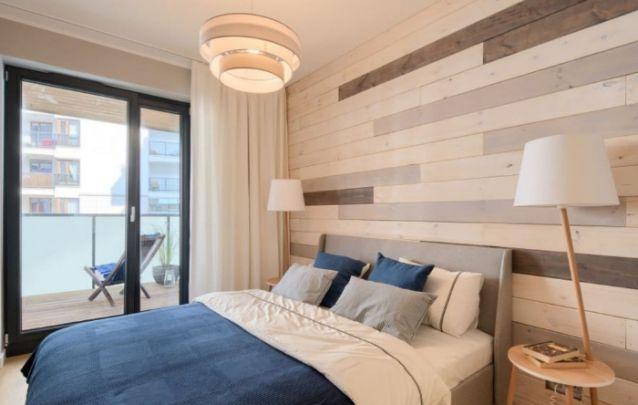 A parede feita de tábuas traz destaque para trás da cama