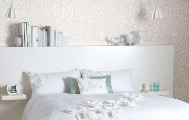A parede atrás da cama com um padrão que lembra o crochê, deixa a decoração de quarto mais romântica e delicada