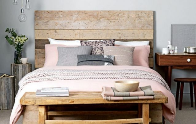A cama feita com madeira de demolição traz um toque rústico à decoração