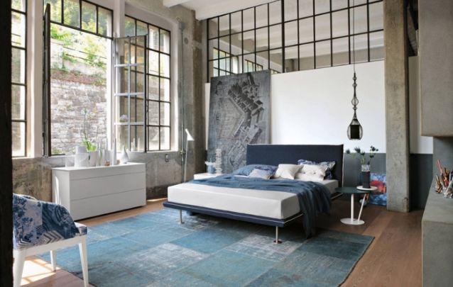 O concreto aparente, o pé direito alto e os acabamentos metálicos trazem um toque industrial para esta decoração de quarto