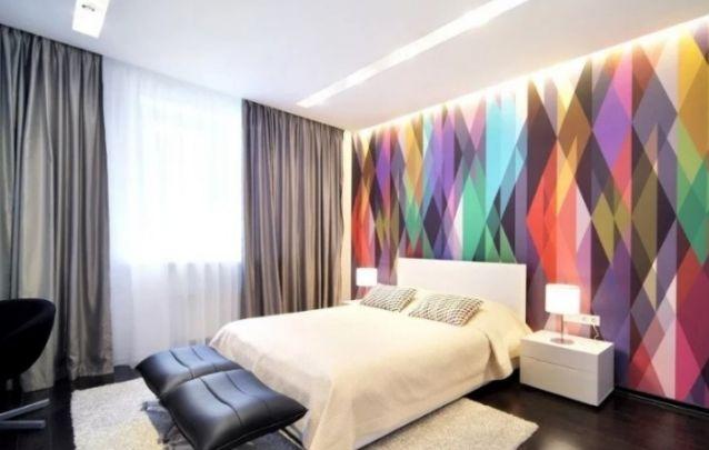 A parede colorida atrás da cama deixa quebra a sobriedade do restante do quarto