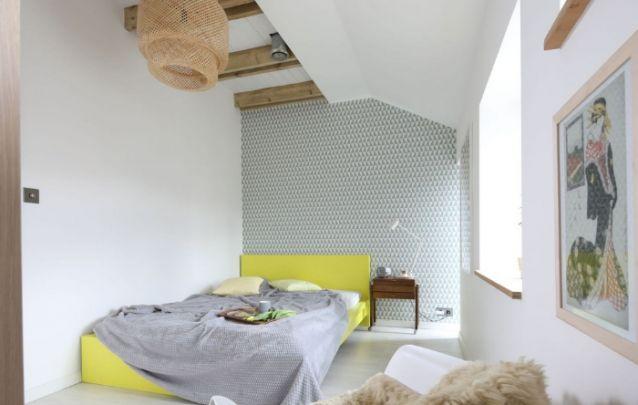 Uma cama amarela para iluminar o quarto pequeno