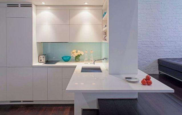 Para esta pequena cozinha em L optou-se por um estilo clean e predomínio do branco