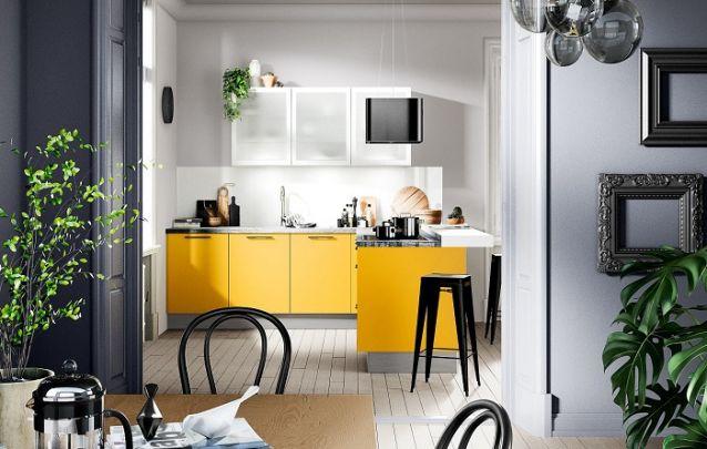 Os armários planejados em amarelo trazem um toque vibrante para esta cozinha pequena em L