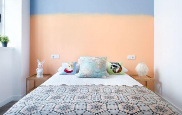 Quarto feminino pequeno com uma parede de destaque atrás da cama
