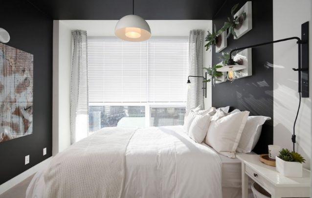 Apesar das paredes escuras, o restante da decoração clara traz a sensação de um ambiente maior