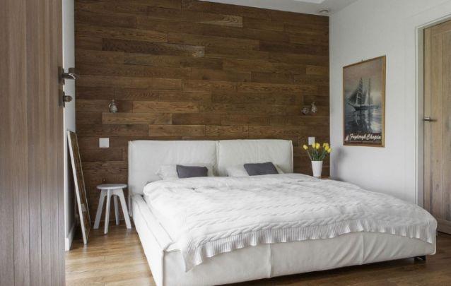 A parede de madeira atrás da cama deixa este ambiente moderno com traços do estilo rústico