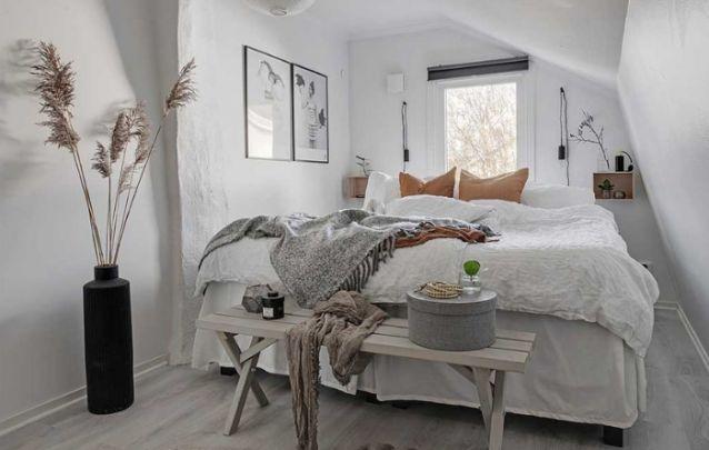 O banco na frente da cama é uma opção multifuncional para este quarto pequeno