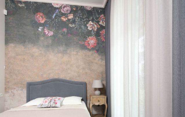 O papel de parede atrás da cama traz acabamento para o pequenino cômodo