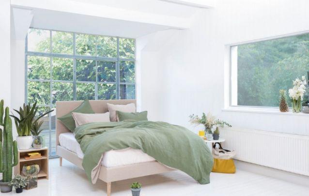 Quarto feminino pequeno com parede de vidro atrás da cama
