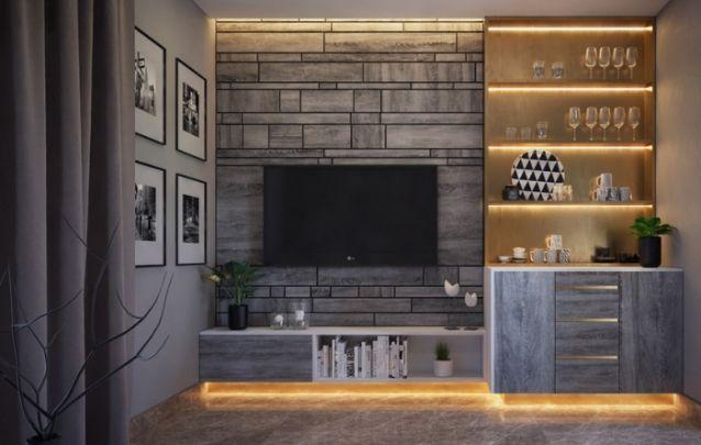 Este painel de tv planejado foi montado a partir de madeiras na tonalidade cinza, as quais foram alinhadas para trazer a sensação de ladrilhos, e o mesmo material segue até as portas da base da cristaleira na lateral.