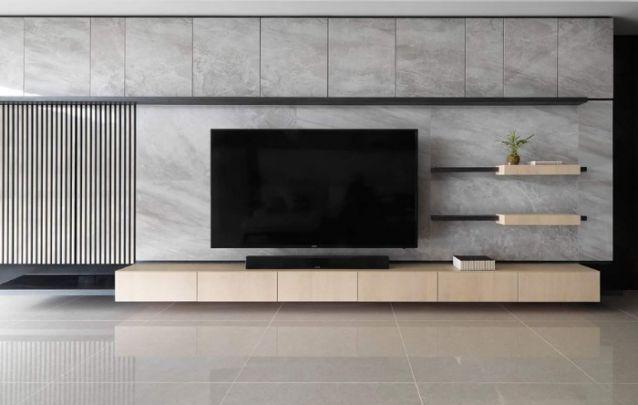 Painel de tv sofisticado e contemporâneo, com um padrão que imita o moderno revestimento de cimento queimado, e conta com prateleiras e alguns espaços para armazenamento.