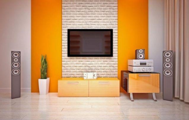 O painel de tv imita uma parede de tijolos bem aparentes, e ainda conta com duas faixas laterais coloridas, para deixar a sala de estar mais despojada. Este é um belo modelo para quem procura um design moderno.