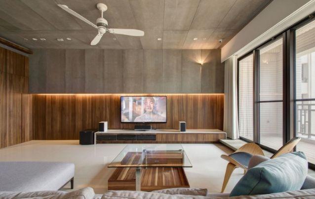 O detalhe em cimento queimado na parte superior, complementa o visual contemporâneo do painel de tv em madeira escura, que se estende perfeitamente por toda a sala de estar.
