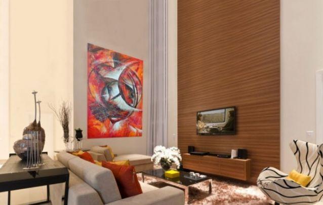 Para trazer continuidade ao visual neste ambiente com pé direito alto, a escolha foi um painel de tv na vertical, que acompanha toda a altura do cômodo. Uma bela opção para quem tem altura avantajada no ambiente.
