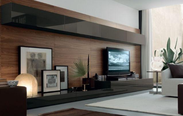 A combinação entre o tom amadeirado marcante do painel e o marrom escuro dos gabinetes, se torna elegante e fica ótima nesta sala de estar sofisticada. Para completar o décor, alguns quadros e lâmpadas de design apoiados sobre a base inferior.