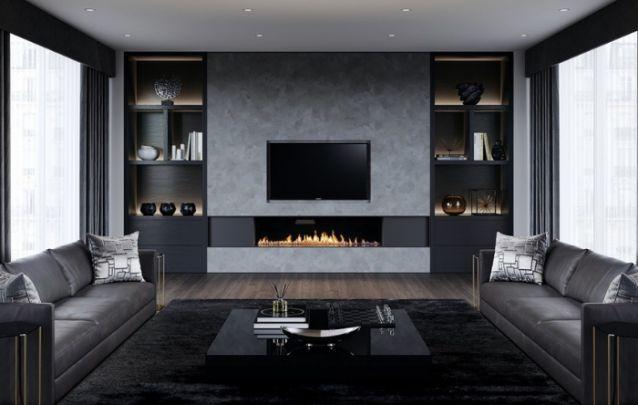 O painel para tv com revestimento que imita o cimento queimado, traz contemporaneidade para o ambiente. Já a lareira e as estantes iluminadas na lateral, agregam sofisticação ao design.