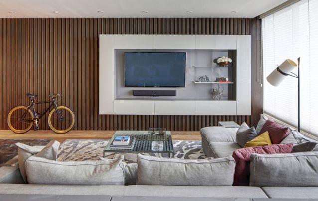 As unidades para armazenamento criam uma moldura ao redor do painel de tv, e as prateleiras acomodadas na parte de dentro, criam um efeito visual especial. Um modelo perfeito para dar um toque de modernidade.
