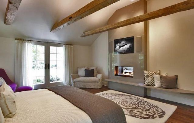 O painel minimalista para acomodar a tv e a lareira, é perfeito para este quarto aconchegante. Além disto, o painel se estende para criar um pequeno banco que também pode ser utilizado como prateleira.