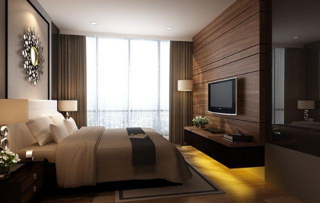 Painel para tv em madeira escura traz sofisticação e a sensação de aconchego para o quarto. As luzes amarelas embutidas na parte inferior, também trazem o sentimento de um ambiente mais acolhedor.