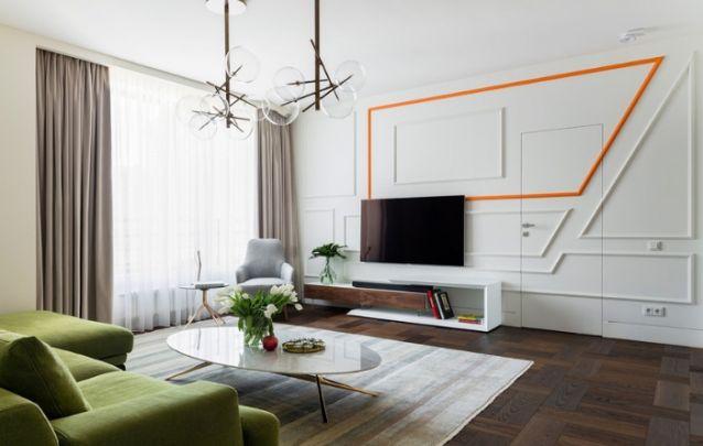 Painéis geométricos e assimétricos feitos de lambri, criam um padrão moderno e tecnológico para acomodar a televisão. E a linha laranja vibrante traz um toque de ousadia para a sala de estar um tanto quanto clássica.