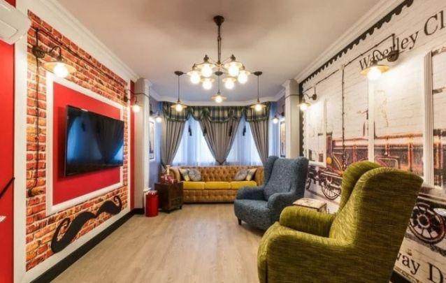 Em cima do papel de parede, uma moldura feita em lambri e uma cor central vibrante, criam o painel para tv perfeito para esta sala ousada e sofisticada. Ouse na sua imaginação!
