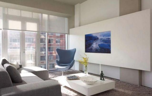 O painel colocado na horizontal cria um efeito super original em contraposição às vigas verticais da parede. A televisão embutida deixa a peça contemporânea e muito funcional.