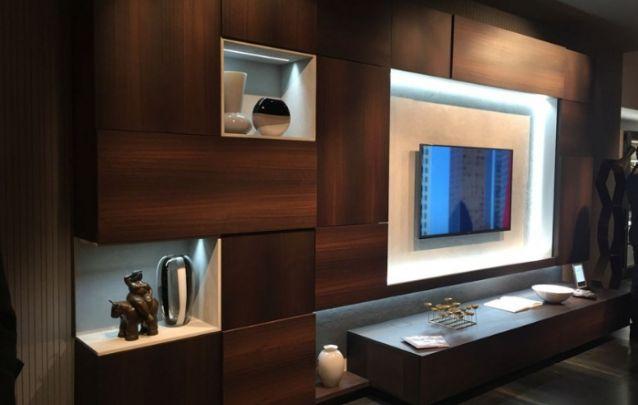 Para esta sala de estar, o painel foi planejado e fica embutido em uma estante sofisticada. As luzes de LED embutidas, suavizam o tom escuro escolhido para este cômodo.