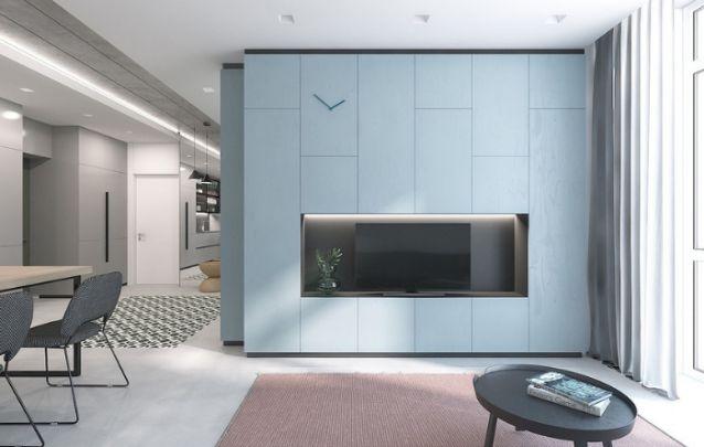Mesmo com a necessidade de espaço extra para armazenamento, uma parte do armário foi reservada para acomodar um painel para a televisão. Cai muito bem nesta sala.